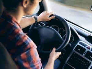 Imagem de um homem dirigindo um veículo, ilustrando nosso conteúdo sobre como comprar um carro no cartão de crédito