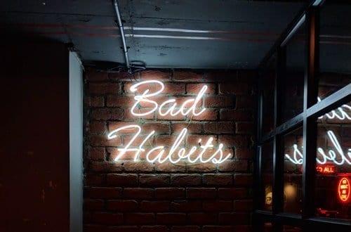 letreiro neon escrito bad habits (em português maus hábitos)