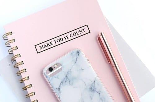 um c aderno, um celular e uma caneta