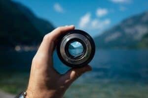 Homem segurando uma lente com grande foco simbolizando o tema como manter o foco