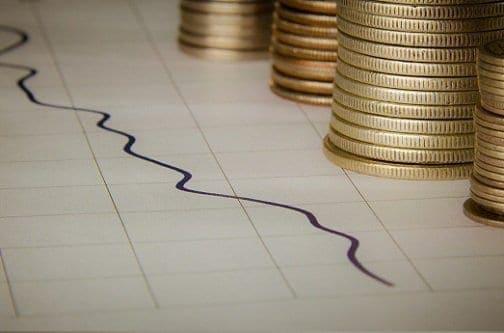 Vários moedas sobre um papel com gráficos simbolizando o tema plano financeiro