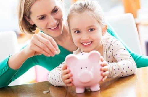 mãe colando moeda num cofrinho de porquinho junto com sua filha