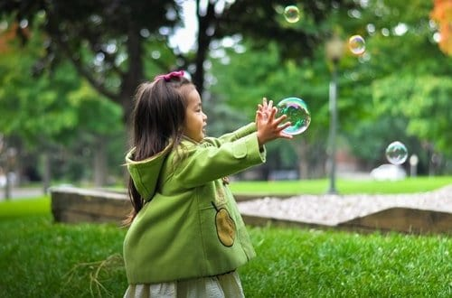 criança brincando com bolha de sabão