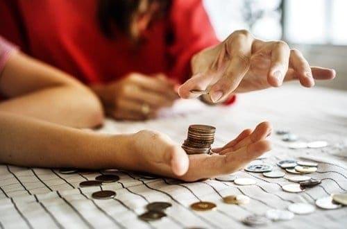 pessoa botando várias moedas na mão de outra
