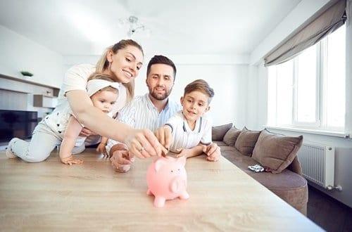 família com seus filhos botando dinheiro no cofre