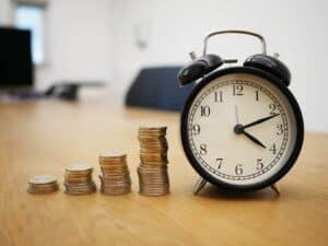 Pilhas de moedas e relógio simbolizando o tema tipos de empréstimos