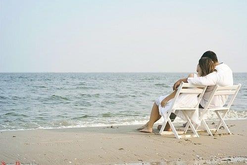 Casal conversando na praia sobre dinheiro simbolizando o tema finanças para casais