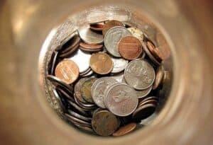 Moedas no fundo de um pote simbolizando o tema Fundo de emergência
