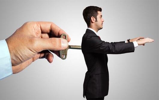 Mão virando uma chave atrás de um homem como se tivesse o controlando