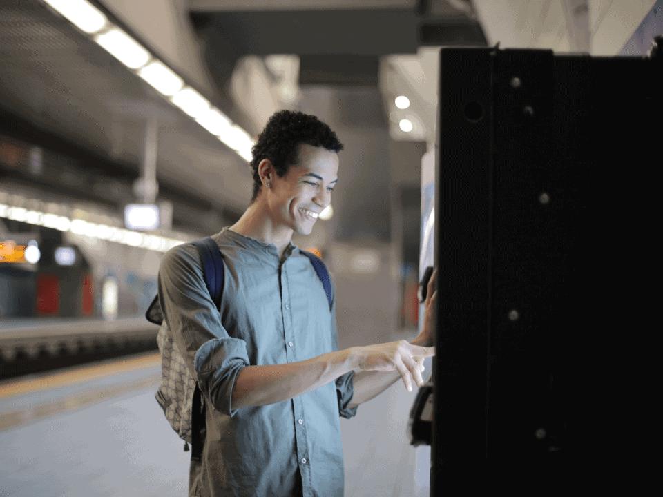 Imagem de um jovem em um caixa eletrônico acessando os serviços essenciais do banco em que tem conta