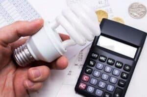 Lâmpada e calculadora simbolizando o tema reduzir o consumo de energia elétrica