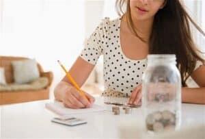 Mulher anotando seus gastos simbolizando o tema Como gastar menos