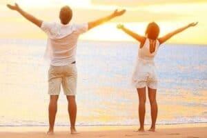 Casal comemorando na praia o alcance da liberdade financeira