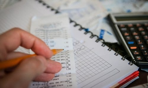 pessoa calculando as contas da casa, representando o conteúdo sobre despesas mensais