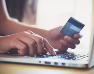 Imagem de uma pessoa usando um computador e um cartão de crédito. Usamos a foto para ilustrar o post sobre limite emergencial de crédito