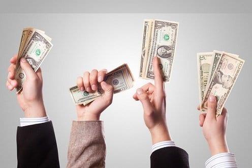 Mãos segurando dólares simbolizando o tema Como ganhar dinheiro sem sair de casa