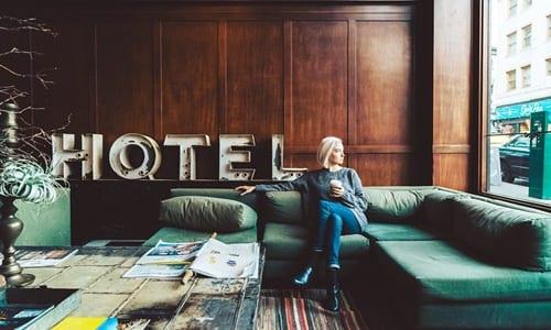 mulher sentada no sofá de um hotel