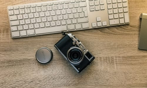 câmera fotográfica e teclado do notebook em cima de uma mesa