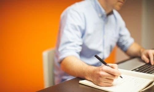 pessoa escrevendo em uma folha