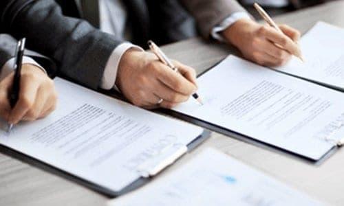 pessoas assinando contratos, ilustrando o conteúdo sobre como montar um pequeno negócio
