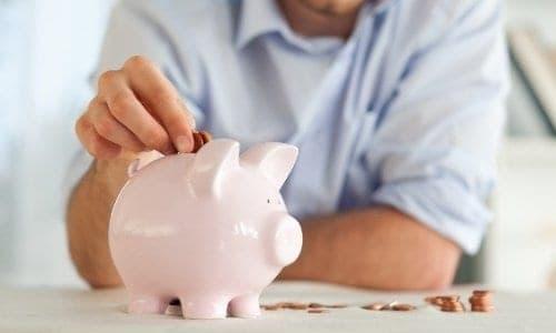 homem botando moedas em um cofre de porquinho