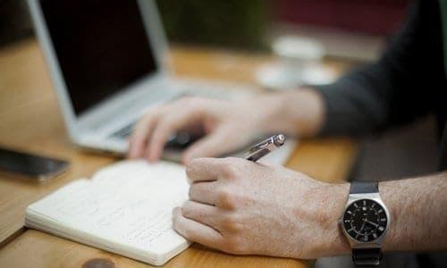 pessoa escrevendo em uma caderneta