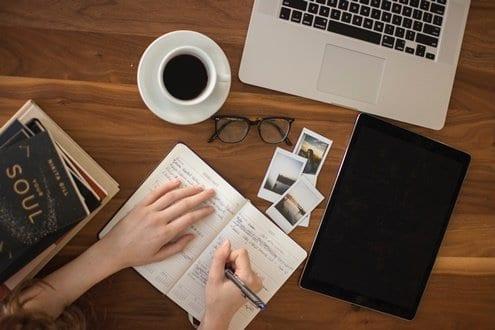 Mulher anotando no caderno os hábitos para implementar