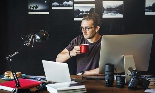 homem sentado em seu escritório com uma caneca na mão fazendo freelancer