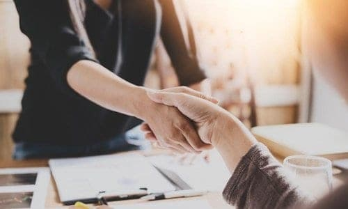 duas pessoas apertando as mãos fechando um contrato freelancer