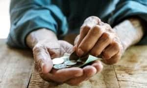 homem segurando moedas e cédulas de dinheiro na mão