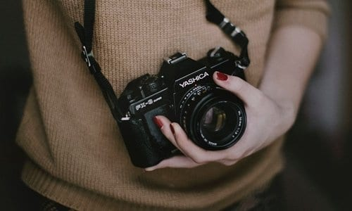 pessoa com uma câmera fotográfica no pescoço e segurando-a na mão esquerda