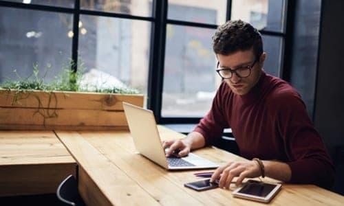 homem mexendo no celular e no notebook ao mesmo tempo
