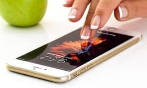 pessoa mexendo no celular e buscando um aplicativo para economizar bateria