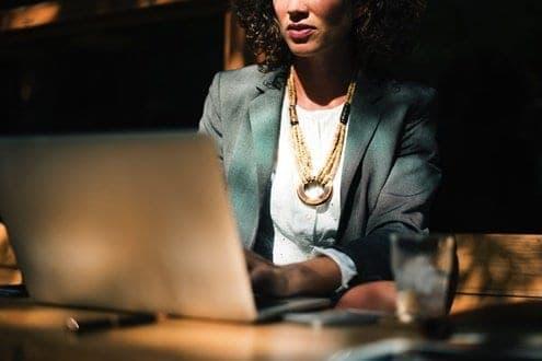 Mulher pesquisando no notebook sobre a força do hábito