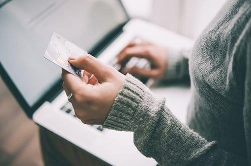 mulher segurando um cartão de crédito enquanto mexe no notebook simbolizando programas de pontos