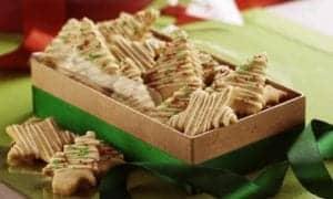 biscoitinhos de canela em forma de estrelas e árvores de Natal dentro de uma caixa retangular