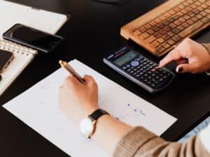Imagem de uma mulher fazendo cálculos para entender mais sobre o cheque especial