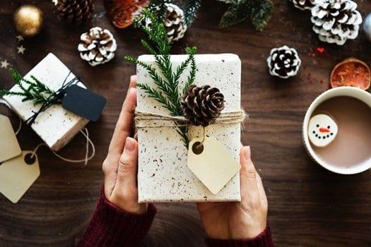 Mãos segurando caixa de presente