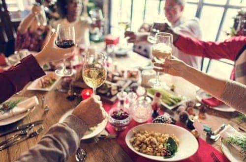 família e amigos brindando em uma ceia de Natal simbolizando receitas de Natal econômicas