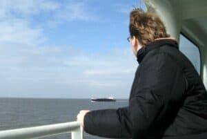 Foto de homem vendo o horizonte em navio simbolizando o tema conquistar metas