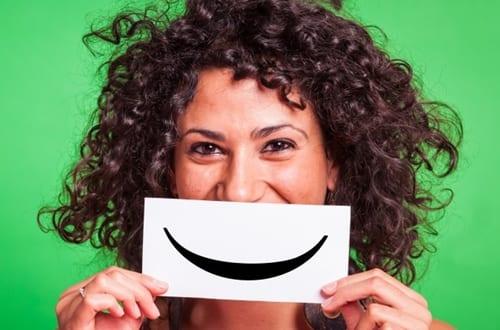 mulher segurando uma folha de papel com um sorriso