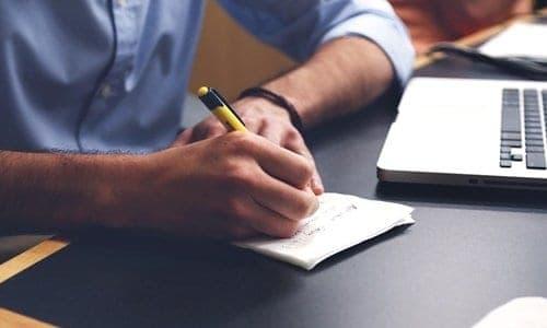 pessoa escrevendo enquanto mexe no notebook