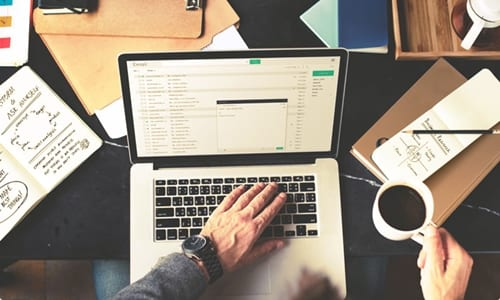 pessoa segurando uma xícara de café enquanto digita no notebook