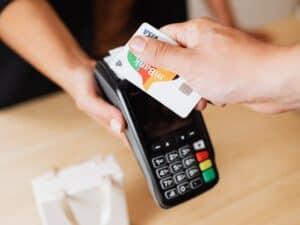 Imagem de uma pessoa passando seu cartão de crédito em uma maquininha enquanto faz compras. A imagem representa nosso post que ensina como usar um cartão vencido