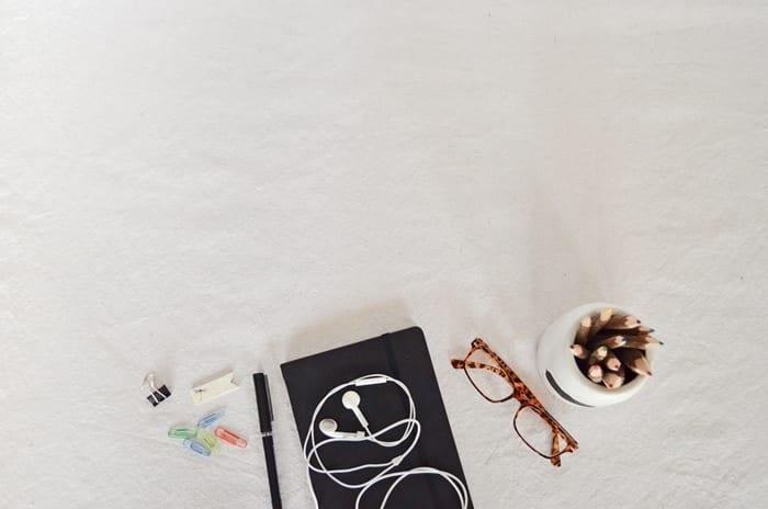 Clippes, fone de ouvido, caneta, lápis e agenda sobre uma mesa