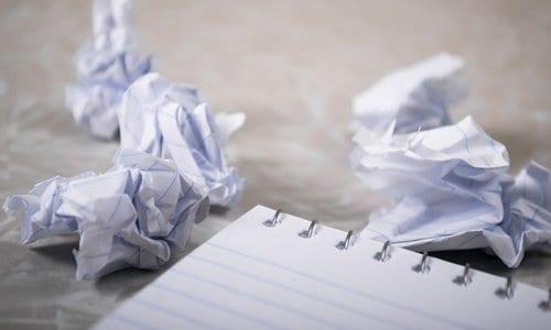 bloco de anotações e ao lado vários papéis amassados simbolizando desistência