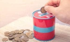 pessoa botando moedas dentro de um cofrinho