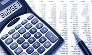 uma calculadora ao lado de uma planilha de contas