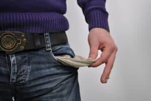 Homem mostrando o bolsos vazio para simbolizar o tema Hábitos que geram pobreza