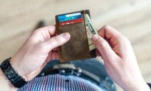 homem tirando dinheiro da carteira
